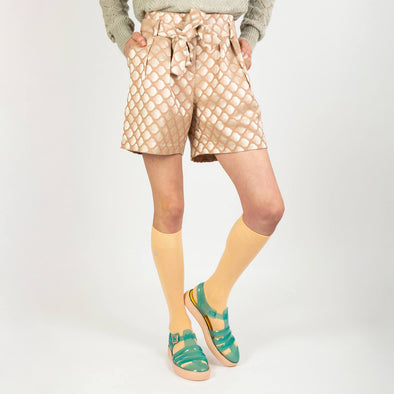 Light rose and metallic beige patterned shorts with a strap to tie at the waist.