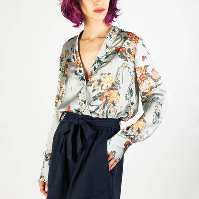 Pastel blue silky wrap top with a fresh flower print.