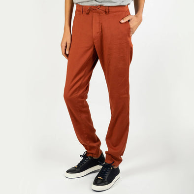Brick colored slightly fitted trousers featuring a strap for extra comfort.