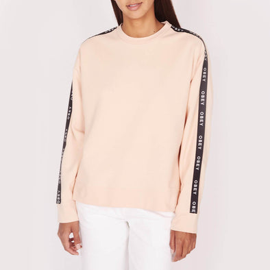 Nude sweatshirt with round neck featuring a personalized OBEY webbing along the sleeves, bottom, collar and ribbed cuffs.