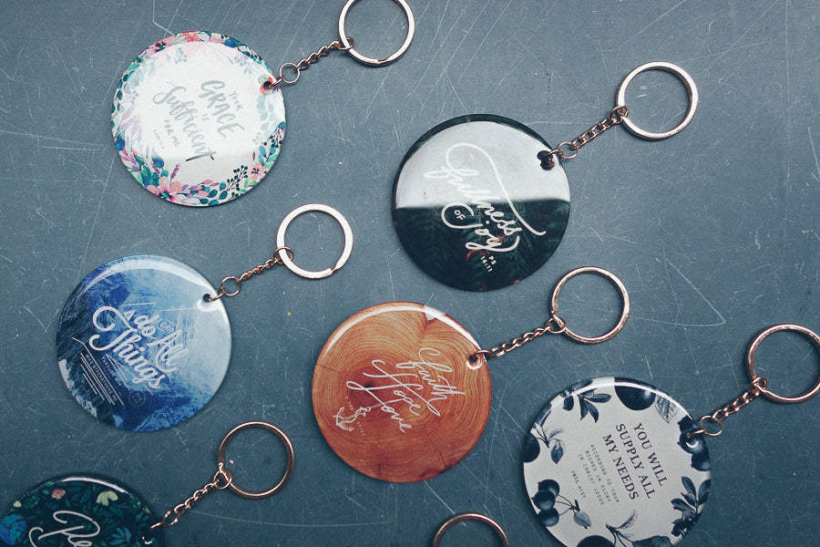 Assorted keychains or key rings with colorful designs and inspiring verses