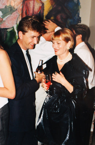 Philippa Riddiford and a male friend holding champagne at a party in front of large paintings