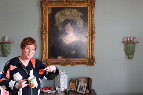 Philippa Riddiford gesturing to the camera in front of an antique framed painting of one of her female ancestors.