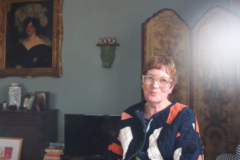 Philippa Riddiford sitting in front of a classic painting in a heavily decorated sitting room with antiques surrounding her