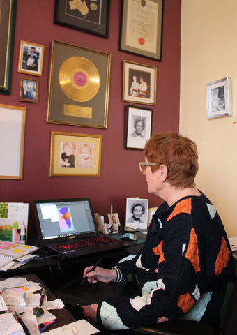Philippa Riddiford is using a wacom tablet to create her paintings at a desk adorned with music industry memorabilia.