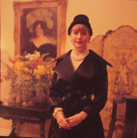 A young Philippa Riddiford standing in front of a collection of antiques in a black dress with a big string of pearls.