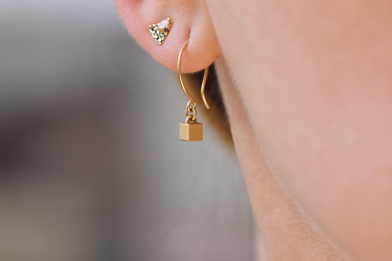 Tiny Cube Gold Earrings On Ears