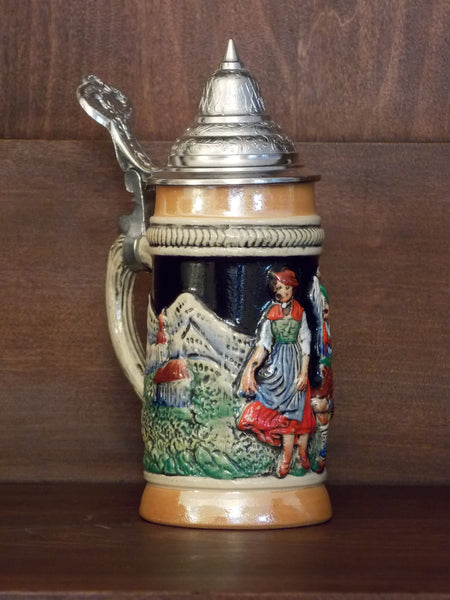 Small German stein with hinged pewter lid and raised design