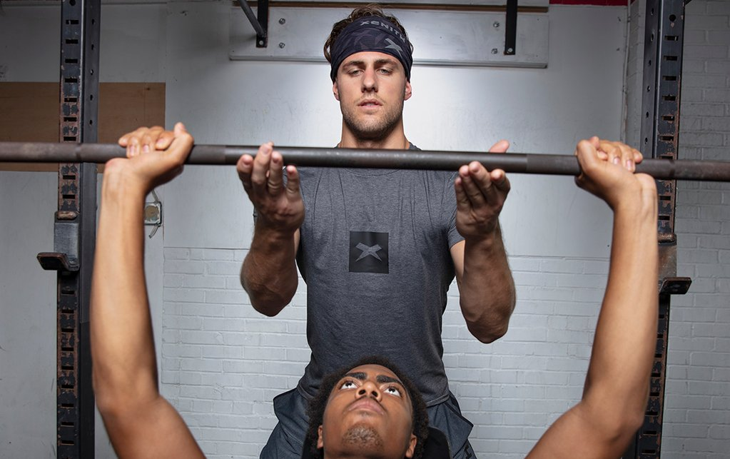 Football players train for the upcoming season on the bench press.