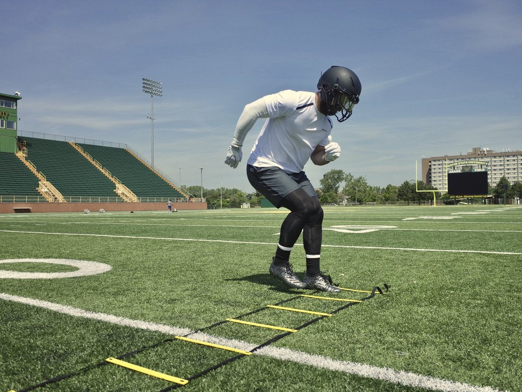 Football player performs ladder drill to improve agility before the season begins.