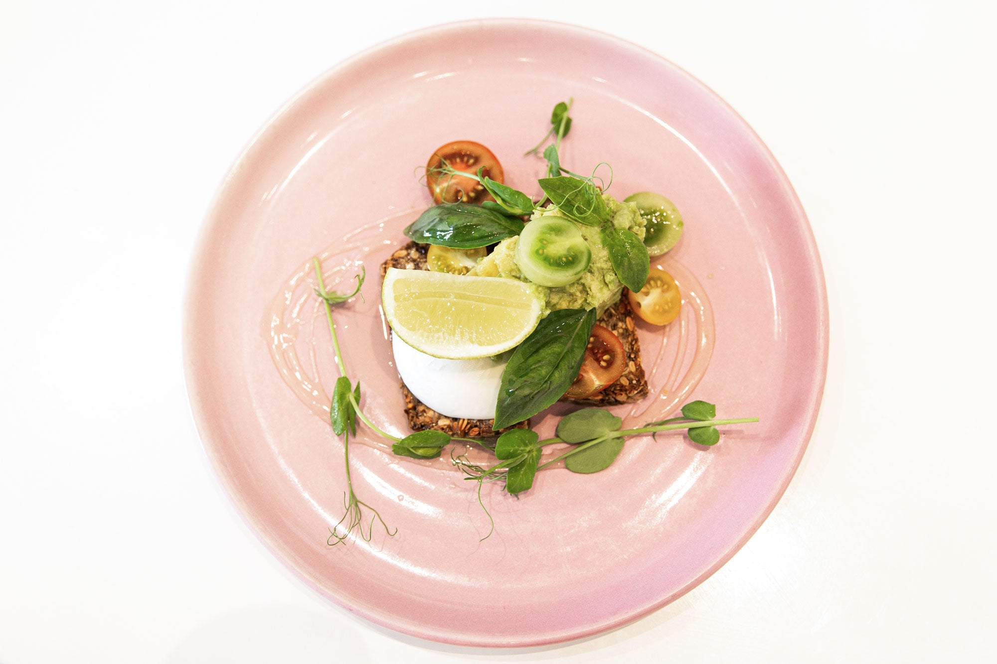 Pink Plate with Seed Loaf, Avocado, Tomatoes at Catroux Cafe Auckland