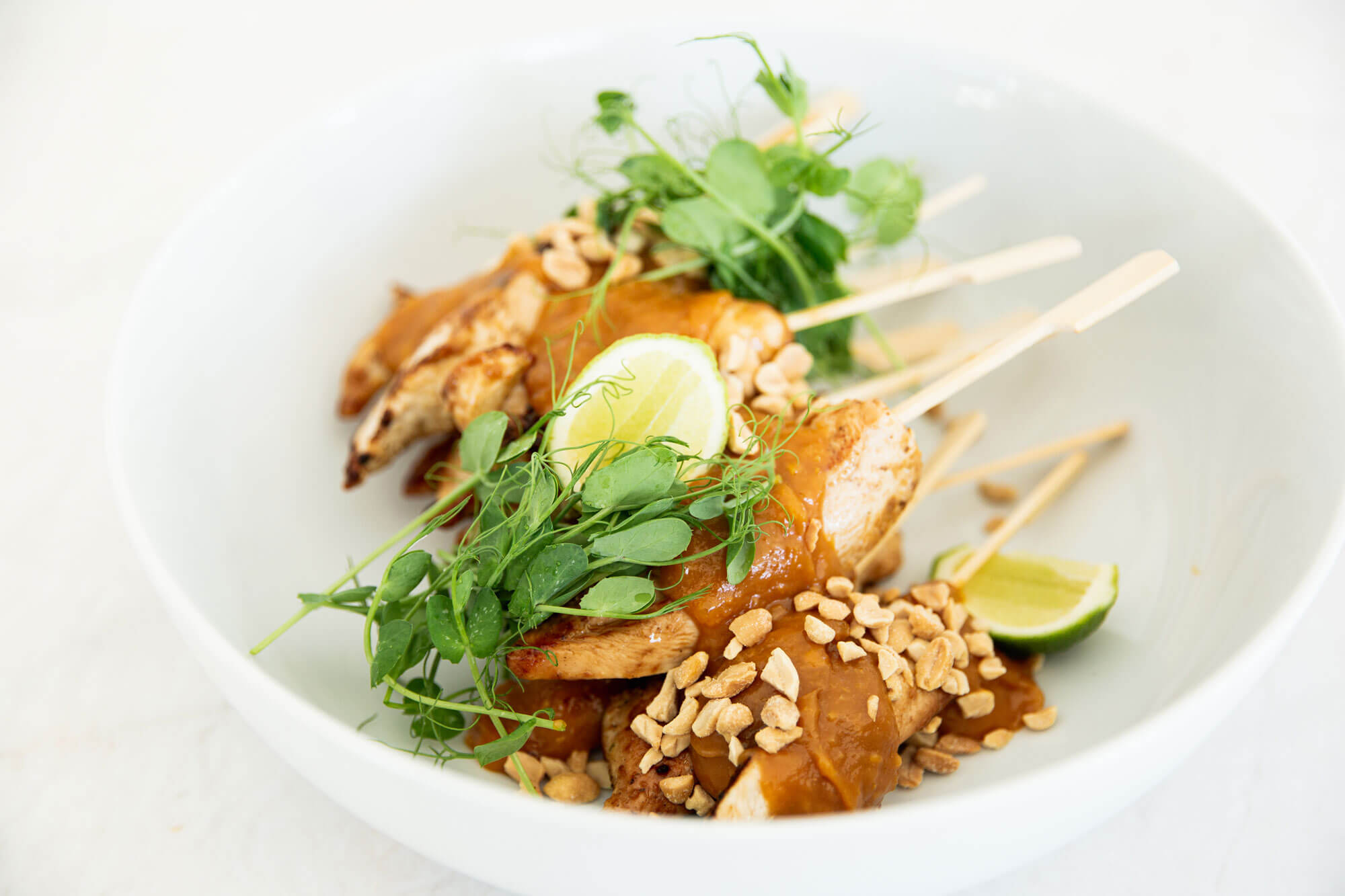 A bowl of chicken satay sticks from Catroux's Lunch, Salad and Dinner Catering Menu