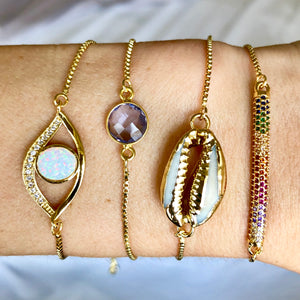 gold adjustable slider bracelets with opal evil eye, purple stone, cowry seashell, and rainbow bar