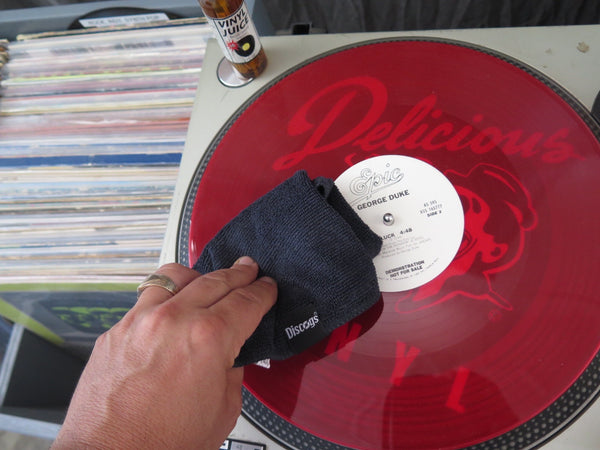 Cleaning a red vinyl record with grey Discogs microfibre cloth