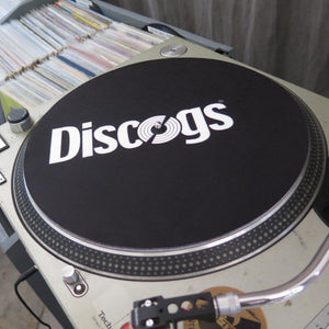 Discogs branded slipmat on turntable next to crates of vinyl records