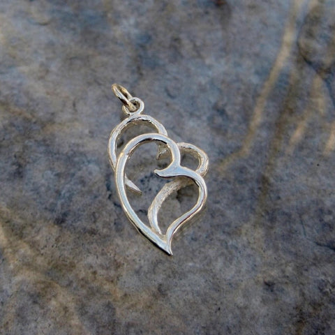 Sterling Silver 2 Hearts Pendant  features an artistic impression of love in which a brushed finish open heart is entwined with a polished heart.