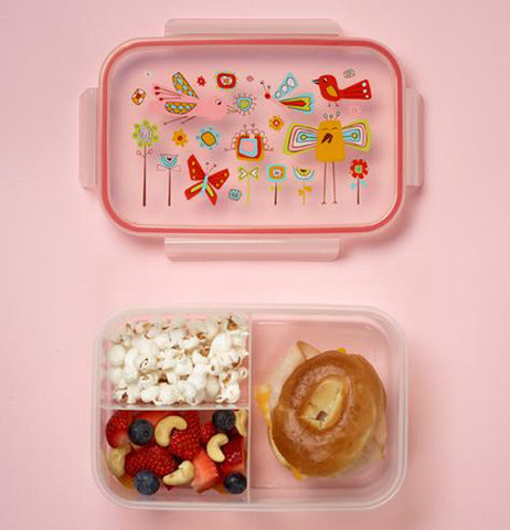 The box is shown open with some food in it. The lid with the birds and the butterflies sits above it on the table.