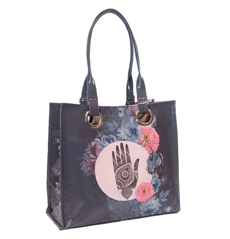 "The ""Hamsa Hand"" Love Tote features a painted hand in the center circle surrounded by pink and purple flowers over deep gray background."
