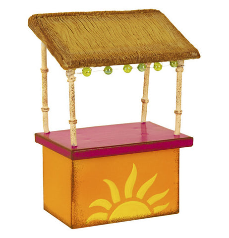 Mini magenta & orange tiki hut that has a yellow half sun on it. Its got an over hang with lights on it being held up with four bamboo poles.