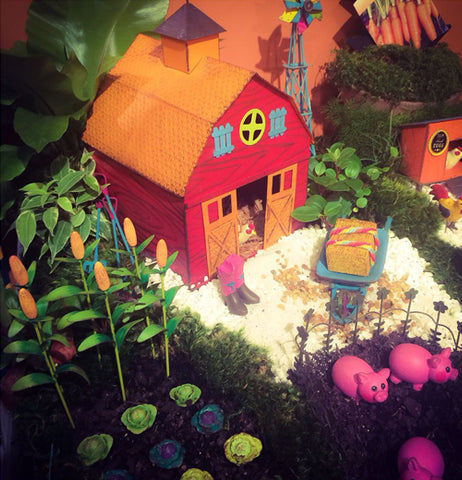 Mini red barn in a fairy garden farm scene.