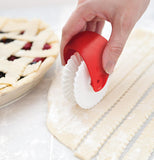 The hand using a Pastry Wheel Cutter to make lattice strips for a pie.