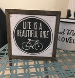 "The box sign saying, ""Life Is A Beautiful Ride"" in its center is shown sitting on a teal green metal shelf in front of a white and black mug."