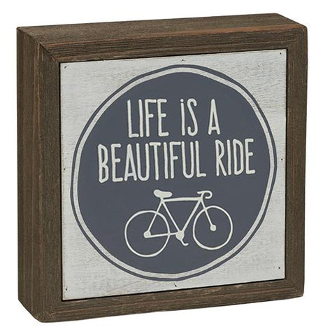 "This wooden box sign shows a blue circle with a white picture of a bike. Above the bike are the words, ""Life Is A Beautiful Ride"" in white lettering."