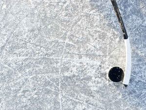 A hockey stick stickhandling a puck on the ice