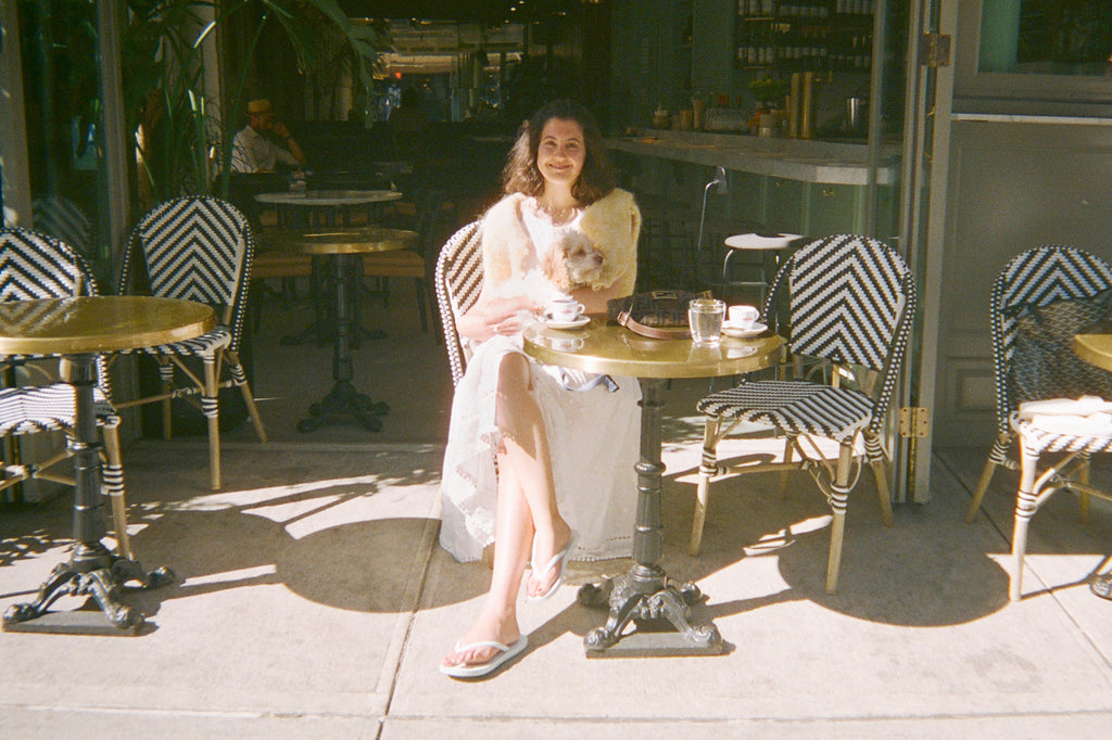 Photo of Jennifer Paccione Angulo in white flip-flops by Tidal New York at a Parisian style cafe in New York City. In true NYC fashion she is wearing flip flops, the perfect shoe for walking a dog.