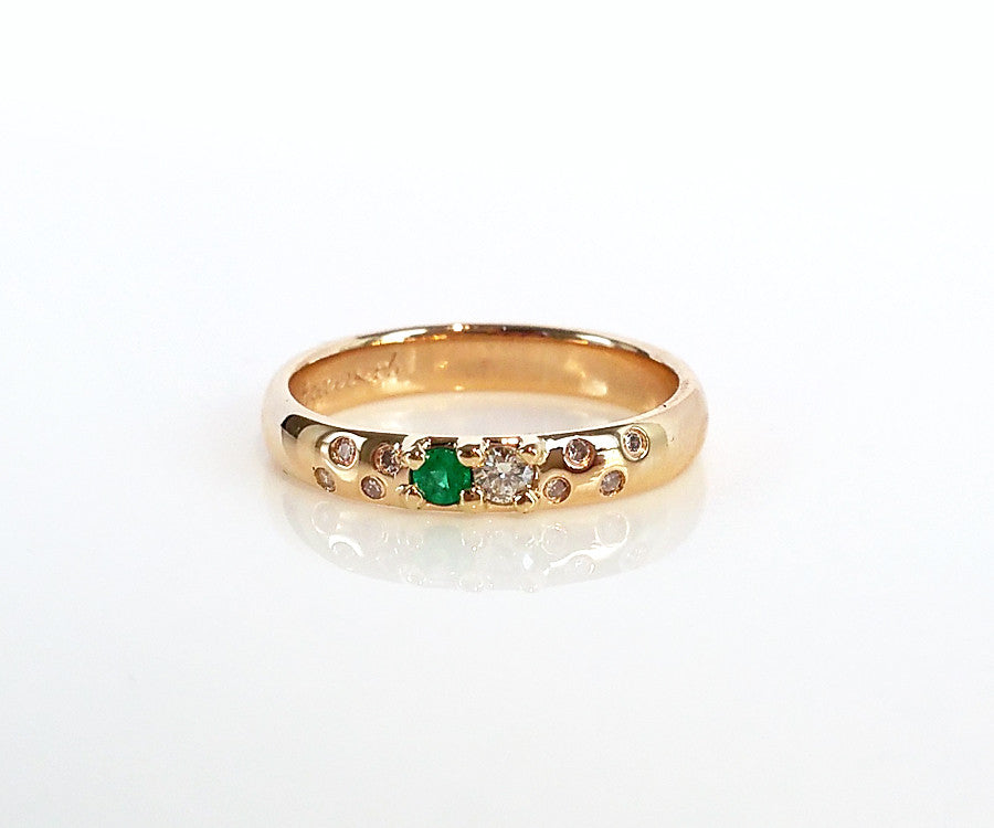 flush set yellow gold diamond and emerald anniversary ring