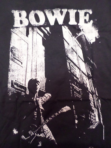bowie black tee vintage look with bowie leaning against building with guitar
