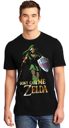 A man smiling while wearing a black t-shirt with an image in the likeness of Link from Zelda
