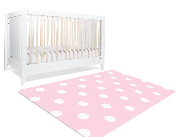 A pink and white polka dotted nursery rug. It has white polka dots on a pink background. This nursery rug is a classic piece to add some classy charm to your baby's nursery.