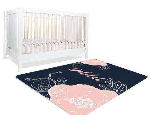 A navy floral rug with a blush flower illustration on it. The nursery rug also has a customized monogram in the center.