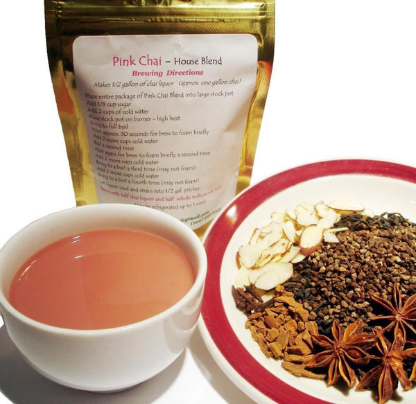 Spicy Pink Chai tea blend- loose spices on a dish, a small white cup of steeped tea, Pink Chai blend in gold packaging