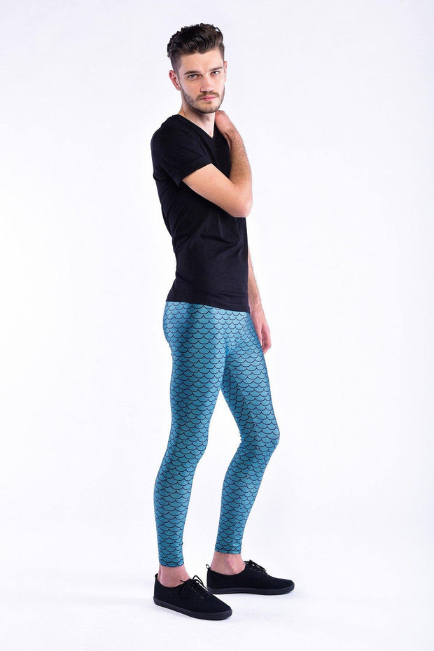 Man posing in Kapow Meggings metallic blue fish scales men's leggings one side view