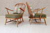 A pair of Ercol armchairs with West African Asoke cushions