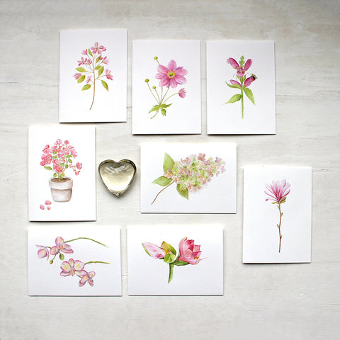 Set of eight note cards featuring pink flowers: star magnolia, amaryllis, crabapple, hydrangea, orchid, Japanese anemone, turtlehead and pink begonia. Painted in watercolor by Kathleen Maunder.