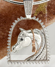 White gold and diamond horse and stirrup pendant by Lesley Rand Bennett.White gold Arabian Horse head with Rose gold tassel framed by a diamond stirrup and diamond bale.