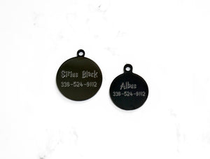 Round Black Dog Tags with mirror finish, hand engraved on a white marble background