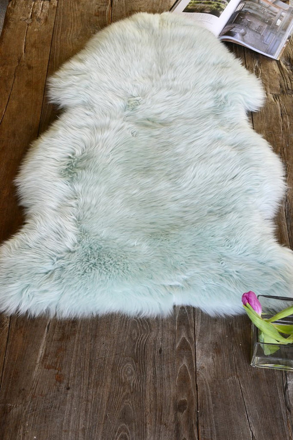 Mint coloured sheep skin pictured lying on the floor with an open book for context
