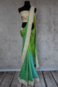 90B421 This green chiffon saree with a pop of blue and embroidered polka dots makes for the perfect Indian outfit for weddings and pujas. Buy this beautiful saree online in USA at our store Pure Elegance.