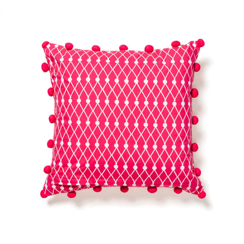 Pink and orange pillow with pom poms at maeree