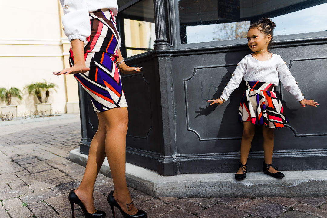 mom and girl against wall wearing colorful chevron skirt