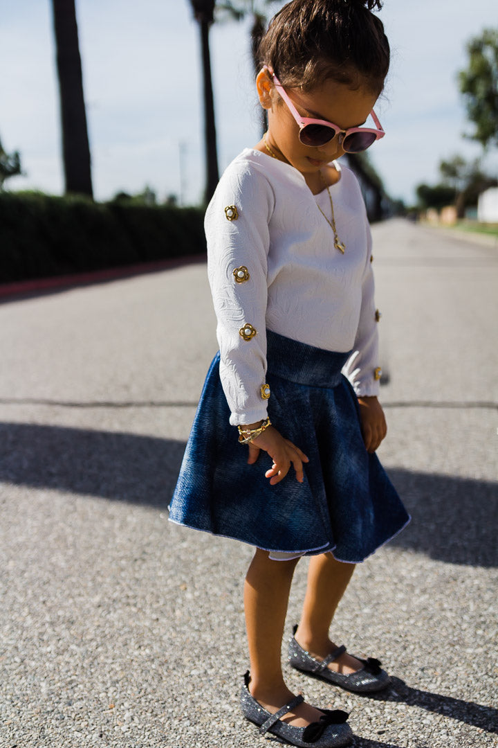 child wearing denim circle skirt and white rose top