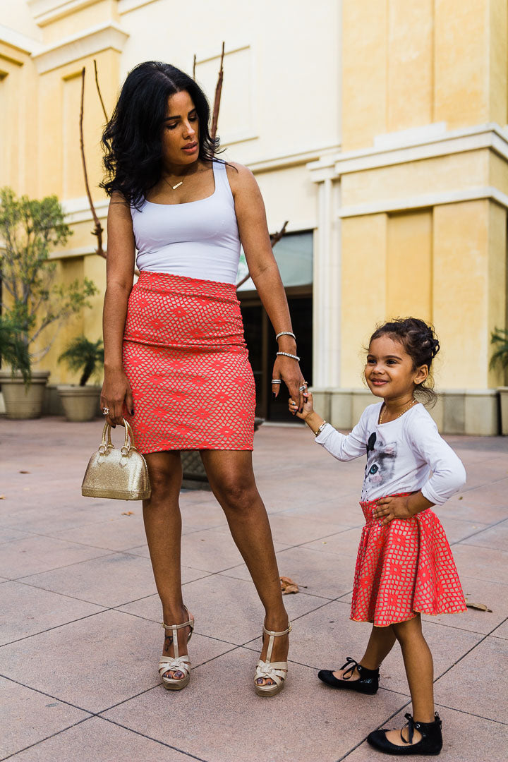 mom and daughter wearing matching coral color skirts