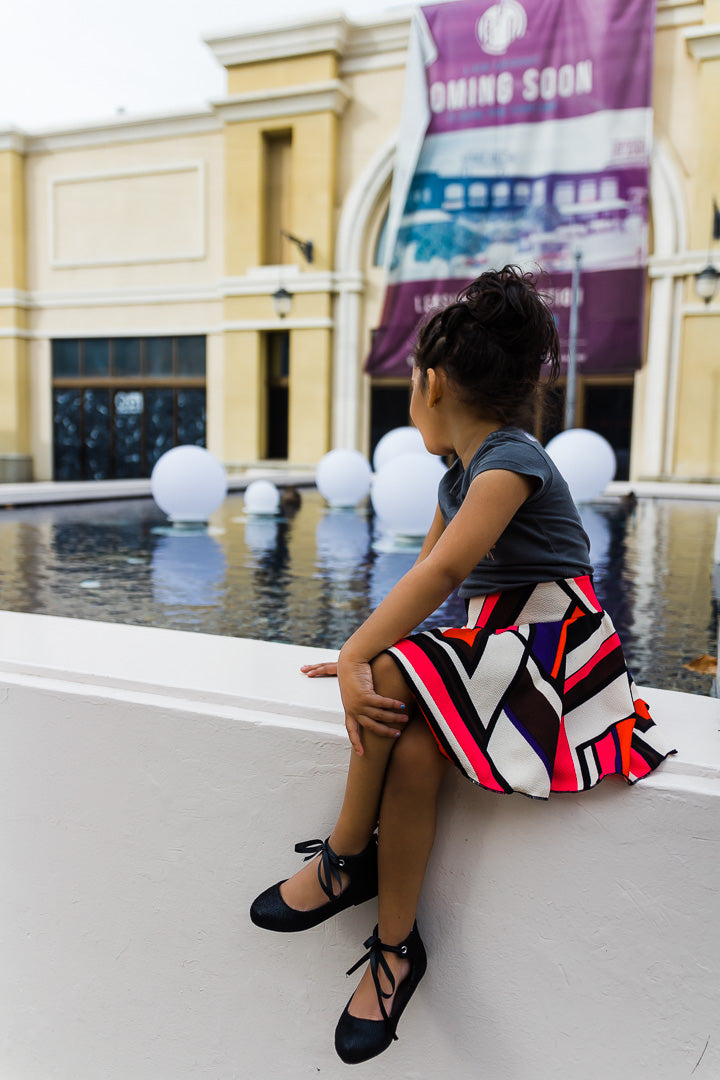 toddler girl by fountain wearing chevron skirt
