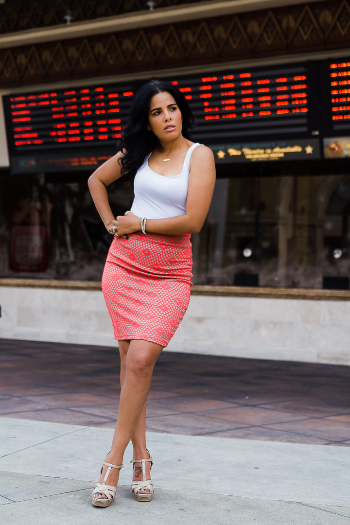woman wearing coral pencil skirt and white top