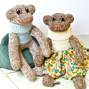 Red Rufus SockMonkeys in jumpers and a skirt. Handmade in Ireland.