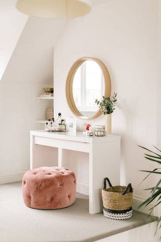 dressing table with pink puf and round mirror
